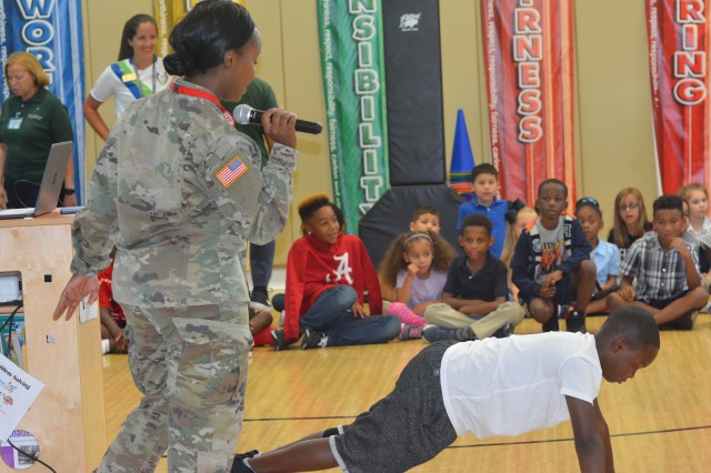 "Staff Sgt. Ayan Mobley tasks one youth at her first-ever ""My Mommy is a Drill Sergeant"" book reading with doing a pushup. As a drill sergeant, she directed Soldiers to do similar exercises during Basic Combat Training. Her book is about life in the Army from her son's perspective."