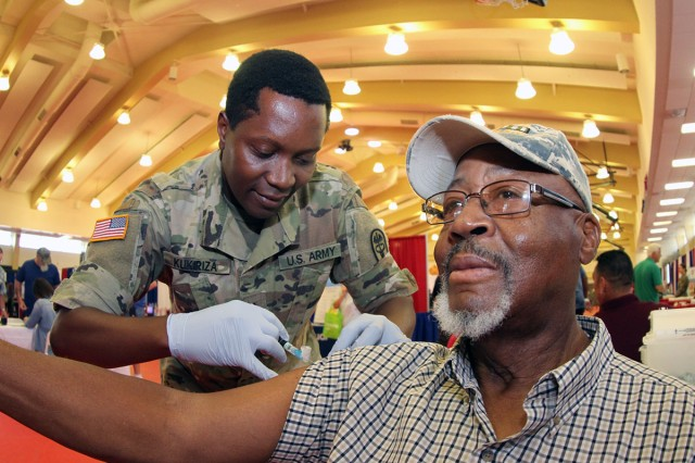 Pfc. Moses Kukiriza, of Reynolds Army Health Clinic, gives a flu shot to retired Master Sgt. Amastee Wright of Lawton, Sept. 20, 2018, during the 40th Annual Retiree Appreciation Days (RAD) open house at the Rinehart Fitness Center. RAHC staff gave over 100 flu shots at the open house.