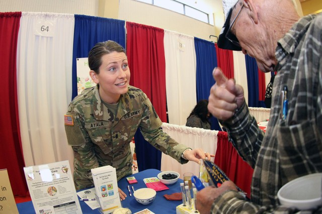 1st Lt. Rachel Ayala, Reynolds Army Health Clinic chief of nutrition care, answers a retiree's question about how much sugar he consumed from the two doughnuts he just ate during the open house.