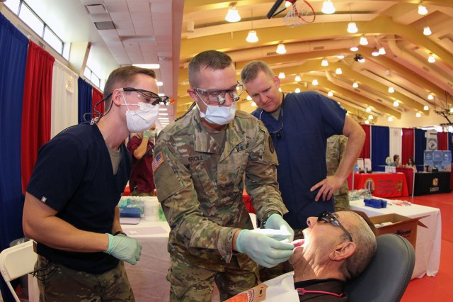 Retired Col. Kenneth Lowmiller, of Lawton, get an oral screening during the Retiree Appreciation Days open house from Capt. Dustin Davis, Maj. Michael Kroll, and Capt. Kyle Leach. Davis and Leach are dentists in the Comanche Advanced Education in General Dentistry 1-year residency program here. Kroll is the AEGD assistant director.