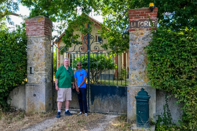 "Tour guide Mike Hanlon, right, and Staff Sgt. Jonell Andre Gittens stand in front of ""La Foret"", a villa used as a hospital during WWI. Sgt. William Shemin stayed here for five weeks after he was wounded."
