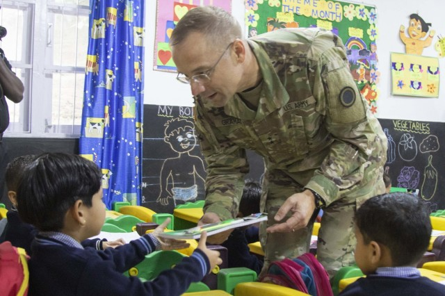 Maj. Gen. William Graham, the Yudh Abhyas 18 force commander, gives school supplies to school children at Chaubattia Military Station, India, Sept. 27, 2018. During the visit, Graham spoke to the children of the importance of education and thanked the teachers for their hard work. This was during Yudh Abhyas 18, a training exercise designed to enhance the readiness and partnership between the U.S. and Indian armies. (U.S. Army photo by Staff Sgt. Samuel Northrup)