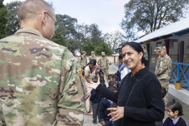 A school faculty member details some of the school's learning objectives with Maj. Gen. William Graham, the Yudh Abhyas 18 force commander, at Chaubattia Military Station, India, Sept. 27, 2018. During the visit, school children were given school supplies and showed off their singing talent to U.S. Soldiers. This was during Yudh Abhyas 18, a training exercise designed to enhance the readiness and partnership between the U.S. and Indian armies. (U.S. Army photo by Staff Sgt. Samuel Northrup)