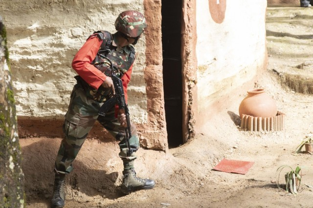 An Indian army soldier prepares to enter a house during a cordon and search demonstration Sept. 25, 2018, at Chaubattia Military Station, India. This was part of Exercise Yudh Abhyas 18, a bilateral training scenario designed to foster a shared tactical and technical understanding between the partnered military organizations. (U.S. Army photo by Staff Sgt. Samuel Northrup)