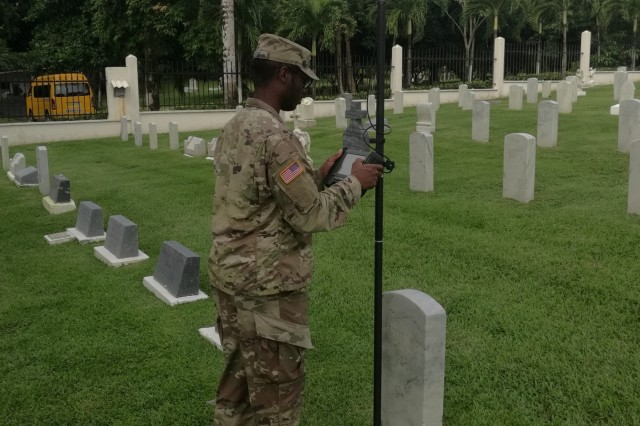 Spc. Jeremy McCrae, an Engineer Soldier, with the 512th Engineer Detachment checks coordinates of an American service member's grave in Corozal American Cemetery in Panama City, Panama, June 28, 2018, as part of a certifying program to ensure precision and accuracy at the final resting places of American service members. The pilot program is supported through a cooperative effort between the American Battle Monuments Commission, Arlington National Cemetery, the United States Army Corps of Engineers, the Army GeoSpatial Center and Product Director Combat Terrain Information Systems. (U.S. Army Photo/Courtesy USACE)