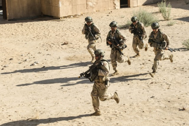 Soldiers of the 11th Armored Cavalry Regiment maneuver through the streets of a compound at the National Training Center, Calif., during an OPFOR training exercise.