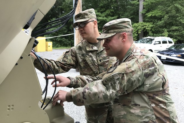 Spc. Justin Latorre, 25C, SATCOM operator from Noble, Oklahoma, and Cpl. Justin Kelly, 25B, Information Technology Specialist from Nudea, New York, perform maintenance on the satellite dish that provides critical communication for the 20th CBRNE command post exercise Sept. 26-28.
