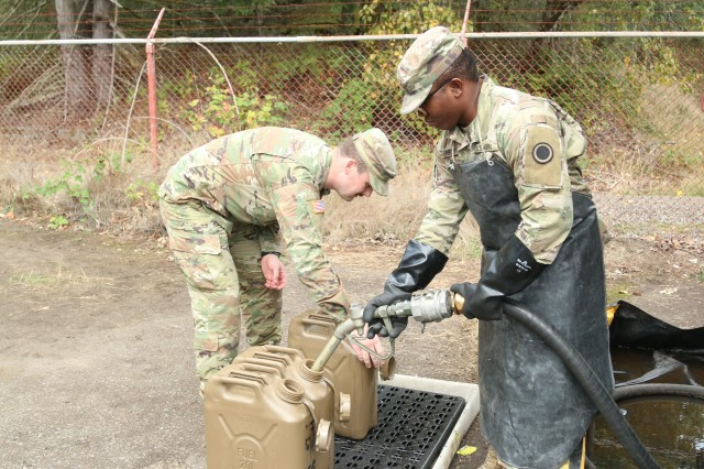 Pfc. Uhuru Evison, a generator mechanic from I Corps Headquarters and Headquarters Company, fills fuel cans for units participating in Warfighter exercise a tactical command post exercise held October 1, 2018 on Joint Base Lewis-McChord.
