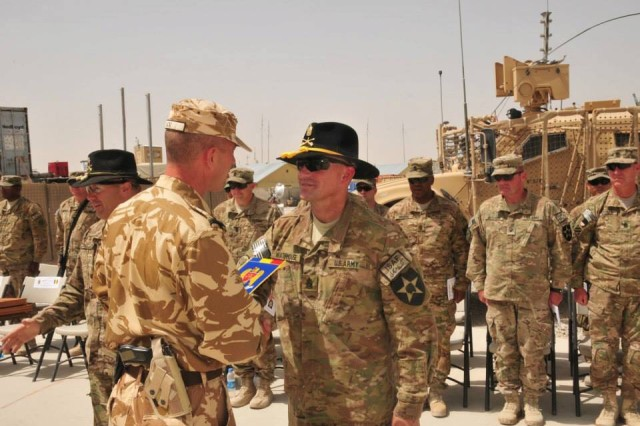A Romanian Army brigade command sergeant major presents a token of appreciation to Command Sgt. Brett Waterhouse after a Transfer of Authority ceremony in Zabul Province, Afghanistan, June 2013. Waterhouse's squadron worked hand-in-hand with two Romanian Army brigades during its nine-month tour in Afghanistan in support of Operation Enduring Freedom.