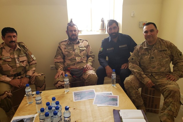U.S. Army Capt. Vicente Garcia, far right, poses for a group photo with three district chiefs of police during an expeditionary advisory package at Zharay Province in Afghanistan.