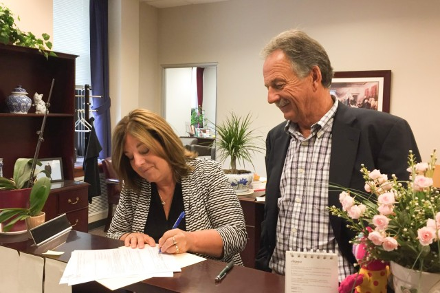 Marcia Larssen, contracting officer and data analytics team lead, Army Contracting Command-Rock Island, signs the final modification to fund that last closeout settlement on the Combat Support Services Contract-Kuwait contract, as Dean Luchsinger, Chairman, Combat Support Associates, looks on, Aug. 14. (U.S. Army Photo)