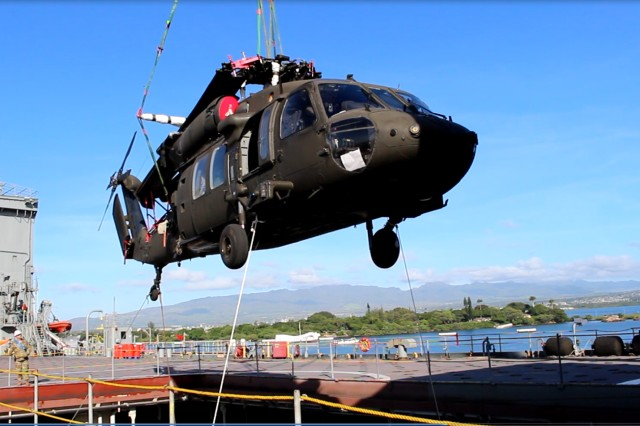 Tag lines on a Black Hawk helicopter frame the Arizona Memorial as the USNS Bob Hope's ship's crane swings it into the hold during port operations at Pearl Harbor on Sept. 21.