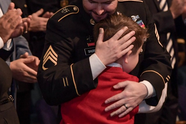 Retired Staff Sgt. Ronald Shurer II embraces one of his sons during the Hall of Heroes ceremony at the Pentagon, Oct. 2, 2018.