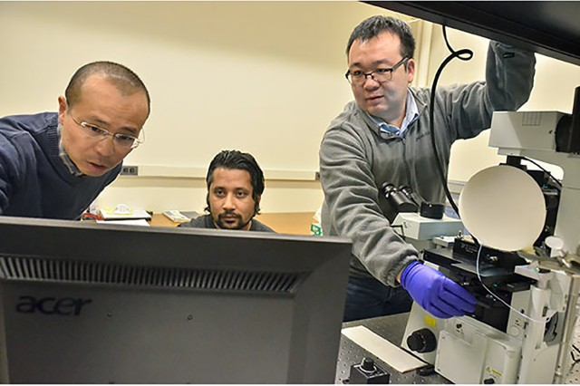 Cornell University Chemistry Professor Peng Chen, left, principal investigator in Army research that resulted in the first real-time visualization of single polymer chain growth, and Dr. Susil Baral, postdoctoral research associate, look at data while Dr. Chunming Liu, right, postdoctoral research associate, adjusts the microscope stage. In an example of the Army's collaboration with academia on technologies critical to battlefield success, scientists at Cornell, funded by the U.S. Army Research Laboratory, researched new analytical techniques for probing polymer dynamics and how to manipulate those dynamics to control polymer microstructure.