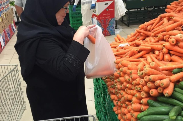 """Becky Moser during a grocery shopping trip to the local Super Panda in Saudi Arabia. She cooks dinner for the team several times during her visits. """"When shopping for vegetables you gather them up and have to go to a kiosk to have them weighed and tagged,"""" she said. """"There is no actual line. You just have to sort of jockey for position. Where we have deli counters, in Saudi Arabia they have olive counters, offering every imaginable color and size."""""""