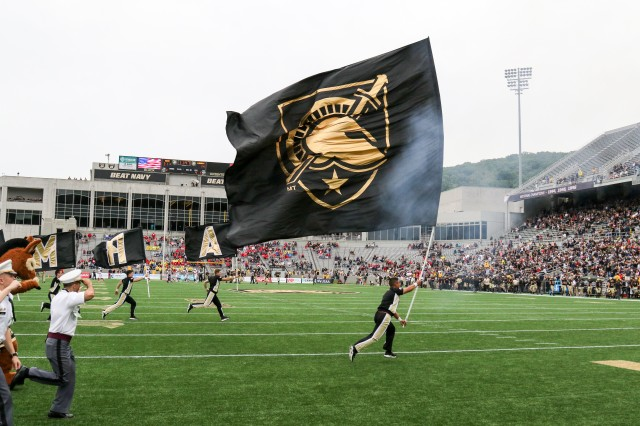 The Rabble Rousers carry flags across the field during a West Point football game.