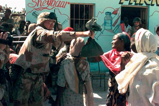 A Civil Affairs Soldier delivers supplies to Somali villagers as part of U.S. humanitarian aid relief efforts in Somalia, in the early 1980s. (U.S. Army photo/RELEASED)