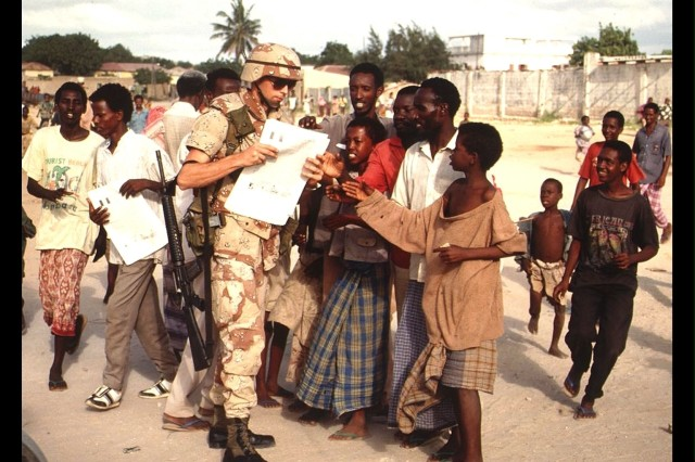 "A Soldier from the 9th PSYOP Battalion distributes the ""RAJO"" newspaper as part of U.S. humanitarian aid relief efforts in Kismayo, Somalia, in the early 1980s. (U.S. Army photo/RELEASED)"