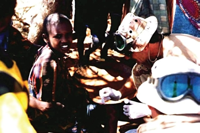 A Special Forces Medical Sergeant assigned to the 5th, Special Forces Group, treats a child as part of U.S. humanitarian aid relief efforts in Somalia in the early 1980s. (U.S. Army photo/RELEASED)