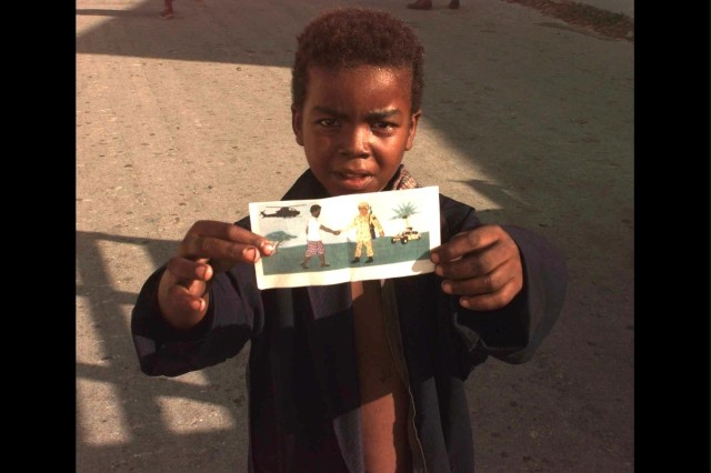 A Somali boy holds a leaflet delivered by the United Task Force PSYOP Campaign as part of U.S. humanitarian aid relief efforts in Somalia, in the early 1980s. (U.S. Army photo/RELEASED)