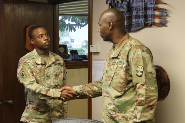 Command Sgt. Maj. Eric R. McCray , 94th Army Air and Missile Defense Command, Command Sgt. Maj. presents Staff Sgt. Clifford T. Burton Jr. with the command's coin of excellence Sept. 28, 2018, at Joint Base Pearl Harbor-Hickam, HI. Burton was recognized by the command for earning the National Association for the Advancement of Colored People, Medgar W. Evers Outstanding Community Service Award.  (Photo by Sgt. Malcolm Cohens 94th Army Air and Missile Defense Command)