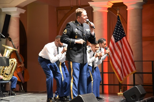 Staff Sgt. Jordan Armstrong, accompanied by members of the U.S. Army Europe Band and Chorus, perform a song at the fifth annual German American Friendship Concert at the Fructhalle in Kaiserslautern, Germany, Oct. 3.