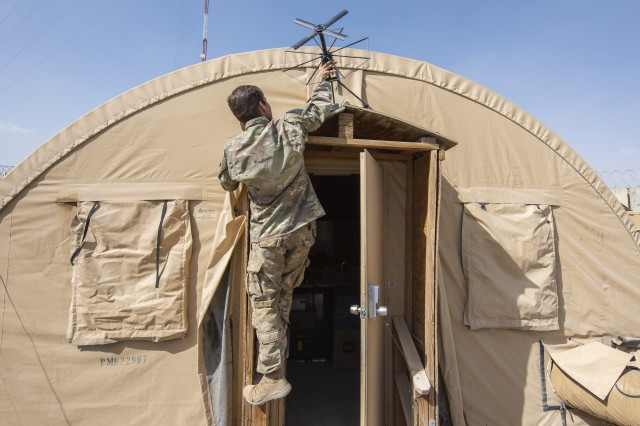 Capt. Tone Biggs, a field artillery advisor with the 1st Security Force Assistance Brigade's 3rd Squadron, positions a communications antenna outside a tent on a tiny compound in the middle of an Afghan National Army camp, Sept. 21, 2018. The compound -- dubbed Crusher and Stallion Area, or CASA, after the mascots of the squadron and their 3rd Infantry Division security forces element -- serves as one of the brigade's tactics to help strengthen Afghan forces at Camp Maiwand, Afghanistan.