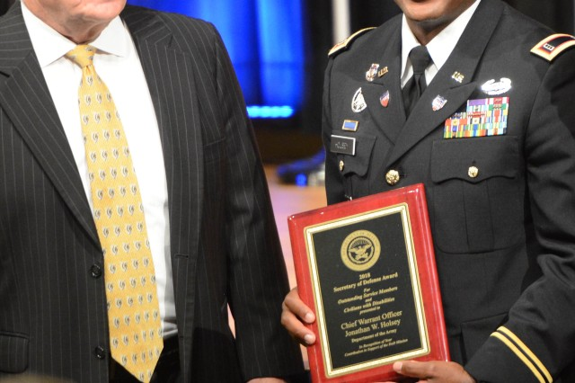 Chief Warrant Officer 3 Jonathan W. Hosley, brigade human technician for the 21st Signal Brigade, Fort Detrick, Maryland, receives the Department of Defense Disability Achievement and Recognition Award at a Pentagon ceremony, Oct. 4, 2018. Presenting it is Kevin Kelly, deputy director, Force Resiliency, Office of the Under Secretary of Defense for Personnel & Readiness.