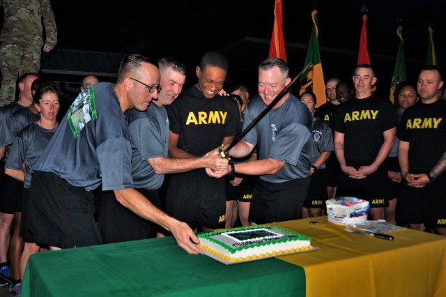 From left, Regimental Command Sgt. Maj. James Breckinridge, Brig. Gen. Brian Bisacre, Pvt. Aaron Woodard, the youngest Soldier present, and Regimental Chief Warrant Officer 5 Joel Fitz prepare to cut the birthday cake following the regimental run Wednesday.