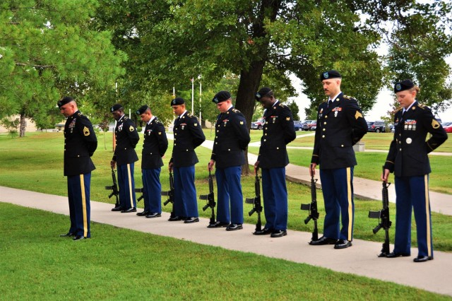 Members of the honor team with 14th MP Bde. bow their heads for a moment of silence during the Memorial Tribute.