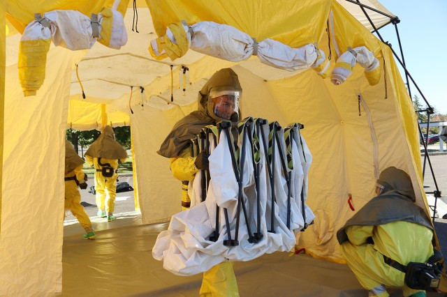Members of the patient decontamination team in full personal protective equipment work at deconstructing the wash tent as they conduct a training at Madigan Army Medical Center on Joint Base Lewis-McChord, Wash. on Sept. 27.