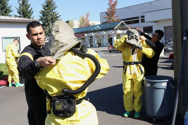 Members of the patient decontamination team assist one another in donning full personal protective equipment at Madigan Army Medical Center on Joint Base Lewis-McChord, Wash. at a training on Sept. 27.