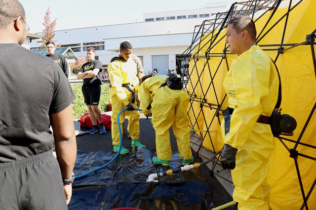 Members of the patient decontamination team hook up water lines to the wash tent as the patient decontamination team at Madigan Army Medical Center on Joint Base Lewis-McChord, Wash. conducts a training on Sept. 27.