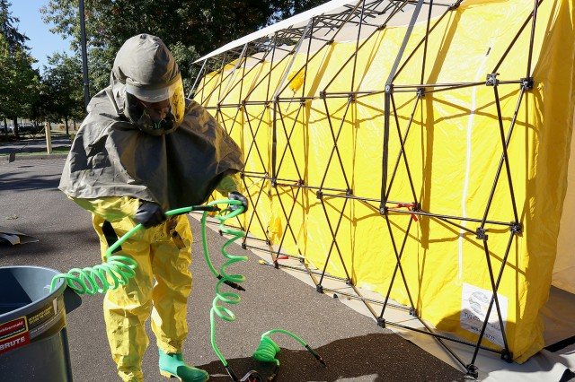 A member of the patient decontamination team in full personal protective equipment works with hoses to attach to a tent to wash patients at Madigan Army Medical Center on Joint Base Lewis-McChord, Wash. at a training on Sept. 27.