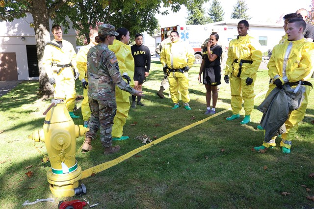 Capt. Rochelle Castro imparts best practices for hooking up the hydrant to the wash tent as the patient decontamination team at Madigan Army Medical Center on Joint Base Lewis-McChord, Wash. conducts a training on Sept. 27.