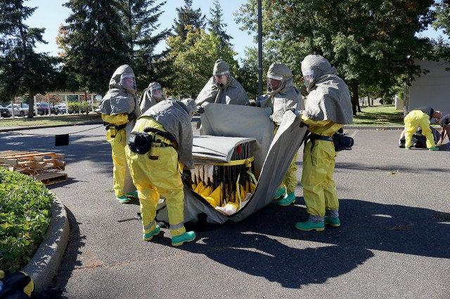 Members of the patient decontamination team in full personal protective equipment fold up the wash tent as they conduct a training at Madigan Army Medical Center on Joint Base Lewis-McChord, Wash. on Sept. 27.