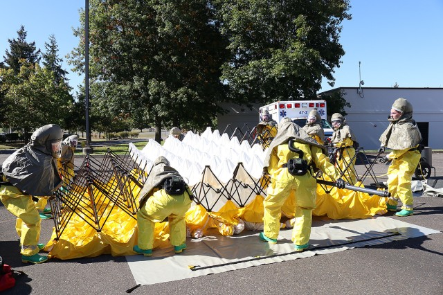 Members of the patient decontamination team in full personal protective equipment at Madigan Army Medical Center on Joint Base Lewis-McChord, Wash. set up a tent to wash patients at a training on Sept. 27.