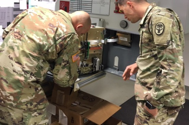 Chief Warrant Officer Richard Hendricks, MEDDAC Bavaria Deputy Chief of Logistics (right), looks over a piece of equipment with a Soldier. Hendricks was recently named the 2017 Army Medicine Health Service Maintenance Technician of the Year.