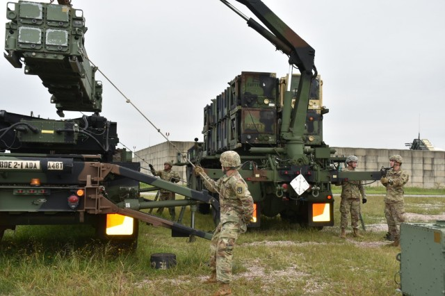 Pvt. Mike Rivera and Pvt. Keaton Kahn from Salem, Oregon maneuver a canister during Alpha Batter, 2-1 ADA PATRIOT Missile Reload Training and receive guidance from Pfc. Matthew Berko from Clark, New Jersey and Sgt. Dustin Pettit from Indianapolis, Indiana.