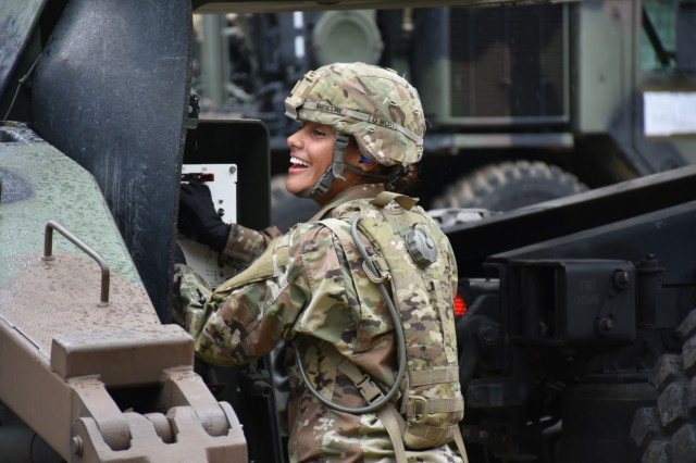 Pfc. Jamie Dekker runs drills with an enthusiastic smile and said she loves training new Soldiers. (U.S. Army photo by Capt. Marion Jo Nederhoed, 35th Air Defense Artillery Brigade)