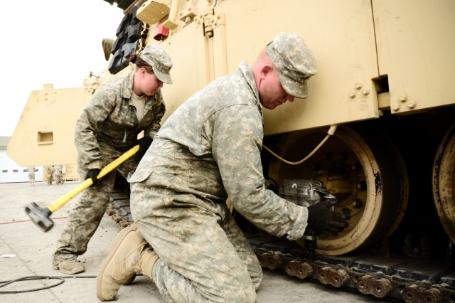 Oregon Army National Guard Spc. Amy Eslinger (left) and Sgt. Scott Eslinger, with H Company, 145th Brigade Support Battalion, replace tracks on an M88A2 Hercules armored heavy equipment recovery vehicle during 3rd Battalion, 116th Cavalry Regiment's gunnery training, April 14, 2018, at the Orchard Combat Training Center near Boise, Idaho.