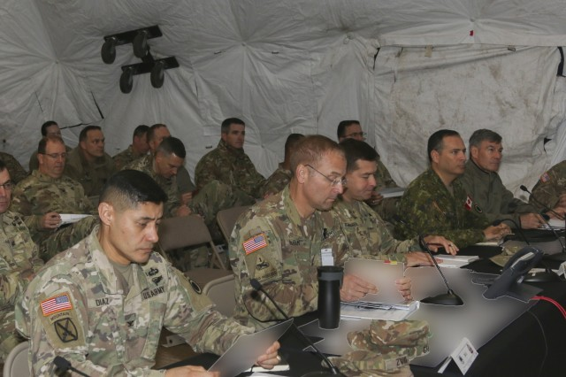 From front left to right, I Corps Chief of Staff Colonel Mario Diaz,  I Corps Deputy Commanding General William Graham, I Corps Operations Sgt. Maj. Victor Ballesteros, Deputy Commanding General -Operations Michel-Henri St-Louis, receive a brief on the current status of the battle simulation during Warfighter Exercise 19-1, a tactical command post exercise that was held from October 2-10, 2018 on Joint Base Lewis-McChord that included units from across America's First Corps and attached components from the Army National Guard. This exercise gave the units the opportunity to hone their skills and test their capabilities through simulated battle drills. (U.S Army photo by Sgt. William Brown) (This photo has been altered for security purposes by blurring classified materials)