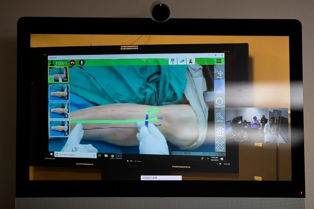 Local staff (inset screen) watch as an augmented reality screen displays a first responder onsite in San Francisco receive telementoring through a procedure by a surgeon located at Naval Medical Center San Diego during a joint exercise with the Navy for Fleet Week in Madigan Army Medical Center's Virtual Critical Care Center on Joint Base Lewis-McChord, Wash. on Oct. 3.