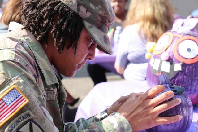 Capt. Quinetta Forby, assign to U.S. Army Japan, decorates a purple pumpkin Oct. 10 outside the Camp Zama Army Community Service building during the second annual Purple Pumpkin event in support of Domestic Violence Awareness Month.