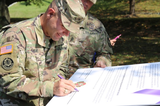 Col. Phillip K. Gage, commander of U.S. Army Garrison Japan, signs a proclamation Oct. 10 outside the Camp Zama Army Community Service building, stating that U.S Army Garrison Japan supports Domestic Violence Awareness Month.
