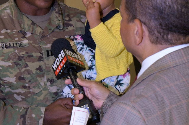 Capt. Aaron Beattie, company commander for the 42nd Clearance Company, holds his daughter, JoAnna, while speaking to reporters following the 42nd's departure ceremony. The unit will conduct will clear Afghan roads of explosive devices