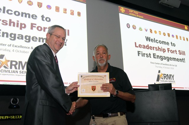 During the Leadership Fort Sill welcome, Joe Gallagher presents LFS student Mike Gradoz, FCoE G6, with a certificate of appreciation for his efforts of creating the application process to apply for LFS. Gradoz also received a cash award of $250.