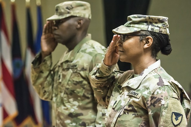 Lt. Col. Shanna Spears (right), commander, 4th Logistics Civil Augmentation Program Support Battalion and Master Sgt. Peter Joiner, senior enlisted advisor, 4th LOGCAP Support Battalion, render salutes after uncasing their unit colors during a transfer of authority ceremony at Camp Arifjan, Kuwait, Oct. 11. (U.S. Army Photo by Justin Graff, 401st AFSB Public Affairs)