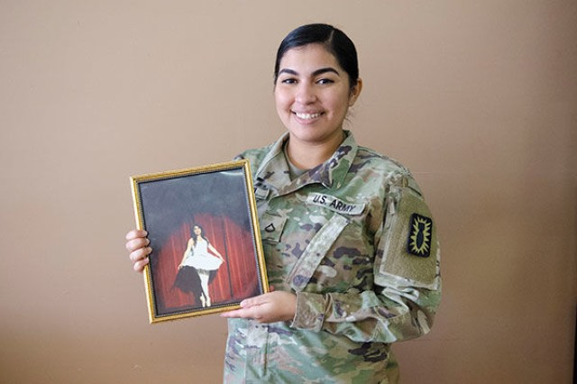 Private First Class Tanairy Franqui-Guzman, Headquarters and Headquarters Detachment, 184th Ordnance Battalion, 52nd Ordnance Group (EOD), holds a portrait of herself performing ballet as a high school student. Franqui-Guzman has studied dance for 10 years. She has performed in about 100 productions.