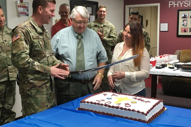 Fort Campbell's most senior physician assistant Terry Davis, (center) assigned to Blanchfield, newest physician assistant 1st Lt. Elizabeth McGrattan, assigned to the Tennessee National Guard, and the hospital's newest Interservice Physician Assistant Program Phase II student 1st Lt. Thomas  Carroll cut a cake Oct. 11 at a luncheon and networking event at the hospital in honor of PA Week.  PA week is observed annually Oct. 6-12. More than 60 physician assistants serve at Blanchfield and units on Fort Campbell supporting Soldiers, retirees and families.